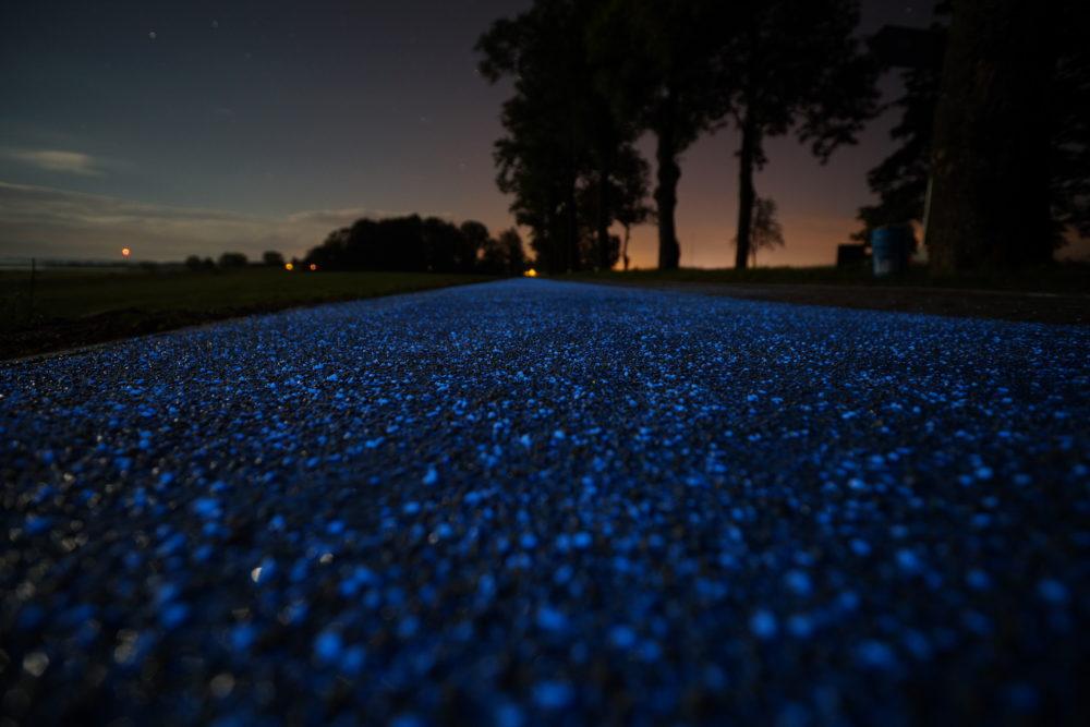 Självlysande partiklar på asfaltens yta.